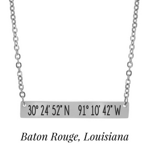 "Silver tone necklace with a bar pendant stamped with the coordinates of Baton Rouge, Louisiana. Approximately 18"" in length."