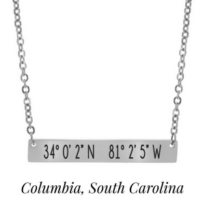 "Silver tone necklace with a bar pendant stamped with the coordinates of Columbia, South Carolina. Approximately 18"" in length."
