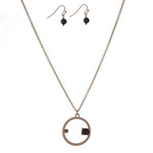 """Dainty gold tone necklace set with a circle pendant, accented with a rhinestone and a black stone. Approximately 16"""" in length."""