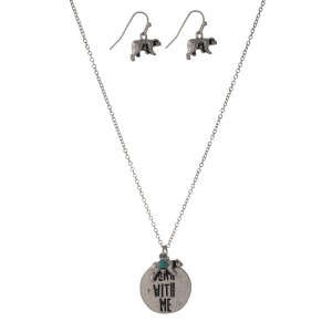 """Dainty silver tone necklace set with a circle pendant stamped with """"Bear With Me"""" and accented with a turquoise bead and matching fishhook earrings. Approximately 16"""" in length."""