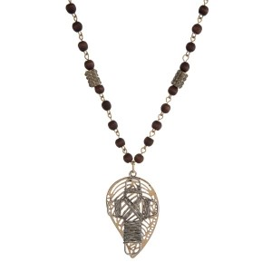 """Gold tone and brown wooden bead necklace with two tone, leaf and cross pendants. Approximately 32"""" in length."""