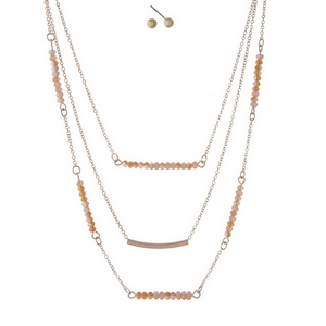 "Dainty rose gold tone, three layer necklace set featuring peach beads, a curved bar pendant and matching stud earrings. Approximately 14"" to 18"" in length."