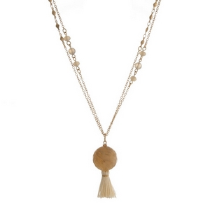 """Gold tone necklace featuring gray faceted beads, a beige bead pendant and an ivory tassel. Approximately 36"""" in length."""