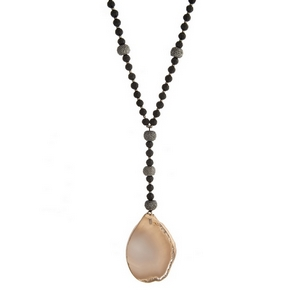 """Gold tone necklace with black faceted beads and a gray natural stone pendant. Approximately 36"""" in length."""