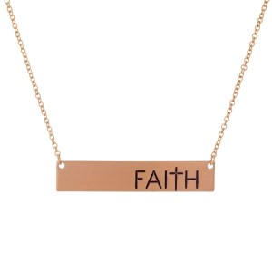 """Dainty rose gold tone necklace with a bar pendant, stamped with """"Faith."""" Approximately 16"""" in length."""