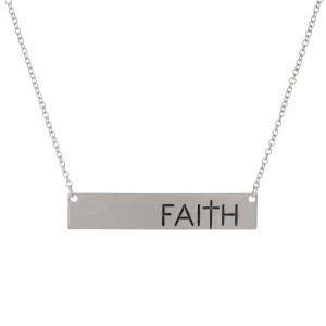 """Dainty silver tone necklace with a bar pendant, stamped with """"Faith."""" Approximately 16"""" in length."""