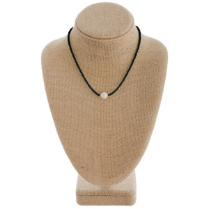 """Short black beaded necklace featuring a pearl accent. Measures approximately 16"""" in length."""