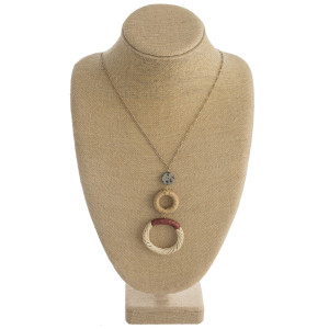 """Long figaro chain necklace featuring a rattan woven double circular pendant with raffia wrapped details and a resin accent. Pendant approximately 4"""". Approximately 38"""" in length overall."""