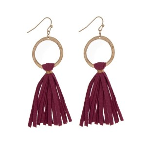 "Gold tone fishhook earrings displaying a circle and a fuchsia suede tassel. Approximately 3"" in length."