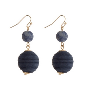 """Gold tone fishhook earrings featuring a sodalite natural stone and a navy blue thread wrapped ball. Approximately 1.5"""" in length."""