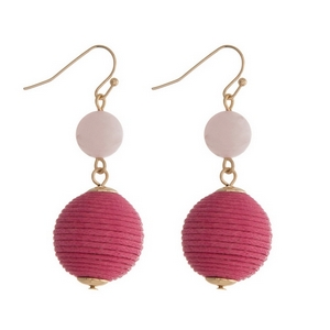 """Gold tone fishhook earrings featuring a rose quartz natural stone and a pink thread wrapped ball. Approximately 1.5"""" in length."""