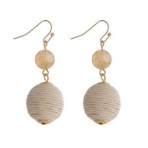 """Gold tone fishhook earrings featuring a beige natural stone and an ivory thread wrapped ball. Approximately 1.5"""" in length."""