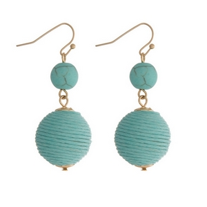 """Gold tone fishhook earrings featuring a turquoise natural stone and a mint green thread wrapped ball. Approximately 1.5"""" in length."""