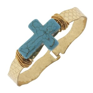Worn gold tone latch bangle bracelet featuring a wire wrapped turquoise stone cross.