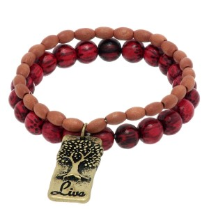 "Brown and red wood beaded stretch bracelet featuring a burnished gold tone plate with a tree stamped ""Live""."