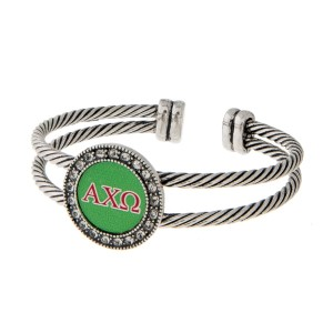 Burnished silver tone officially licensed Alpha Chi Omega cuff bracelet with rhinestone accents.