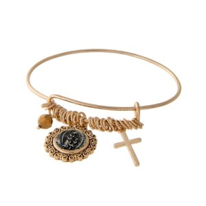 Gold tone latch bangle bracelet with a cross charm, a brown bead, and a two tone angel charm.