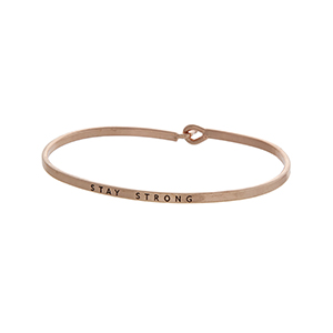"Rose gold tone latch bangle bracelet stamped ""STAY STRONG""."
