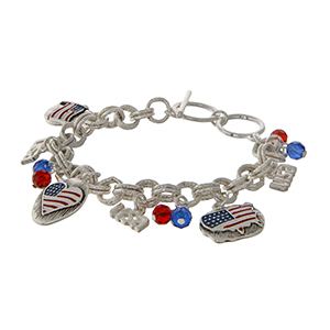 "Silver tone toggle bracelet displaying ""USA"" charms and red, white, and blue flag, heart, and United States of America charms. Approximately 8"" in length."