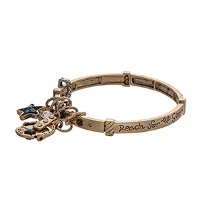 "Gold tone stretch bangle bracelet stamped ""Reach for the Star"" displaying a star charm and a bar with rhinestones."