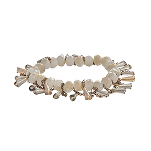 Ivory stretch bracelet with dangling beads and gold tone chains.