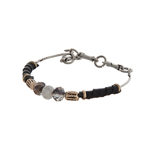 Burnished silver tone latch bangle bracelet wrapped with black cord displaying a three gray beads.