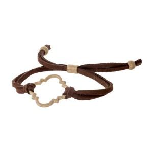Brown suede adjustable bracelet with a gold tone quatrefoil cutout.