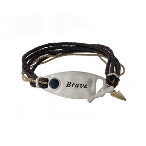 "Brown cord bracelet with a silver tone bar stamped with ""Brave"" and a toggle closure."