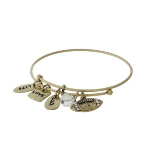 Gold tone adjustable bangle bracelet with a football charm and a clear faceted bead.