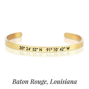 Gold tone cuff bracelet stamped with the coordinates of Baton Rouge, Louisiana.