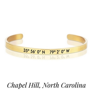Gold tone cuff bracelet stamped with the coordinates of Chapel Hill, North Carolina.