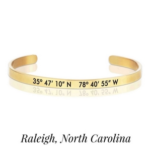 Gold tone cuff bracelet stamped with the coordinates of Raleigh, North Carolina.