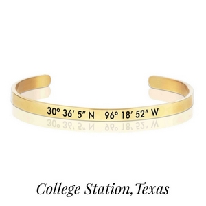 Gold tone cuff bracelet stamped with the coordinates of College Station, Texas.