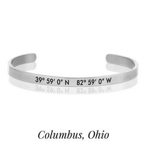 Silver tone cuff bracelet stamped with the coordinates of Columbus, Ohio.