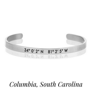 Silver tone cuff bracelet stamped with the coordinates of Columbia, South Carolina.