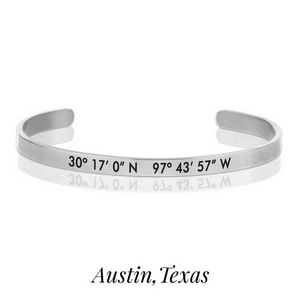 Silver tone cuff bracelet stamped with the coordinates of Austin, Texas.
