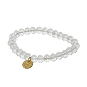 Clear faceted bead stretch bracelet with a hammered gold tone circle charm.