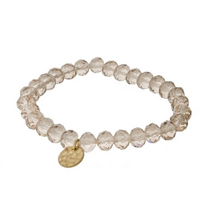 Light brown faceted bead stretch bracelet with a hammered gold tone circle charm.