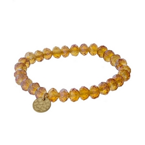 Orange faceted bead stretch bracelet with a hammered gold tone circle charm.