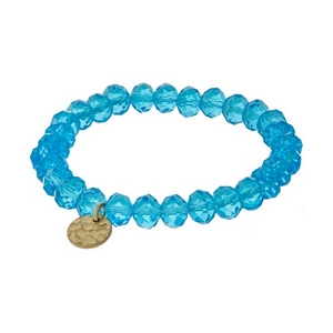 Aqua faceted bead stretch bracelet with a hammered gold tone circle charm.