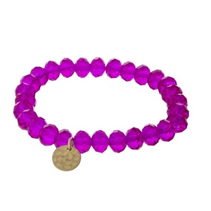 Fuchsia faceted bead stretch bracelet with a hammered gold tone circle charm.