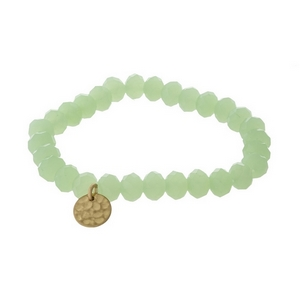 Mint green faceted bead stretch bracelet with a hammered gold tone circle charm.