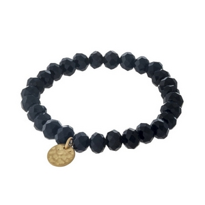 Black faceted bead stretch bracelet with a hammered gold tone circle charm.