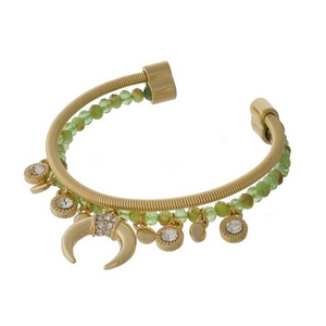 Gold tone and green beaded cuff bracelet with a crescent charm and clear rhinestone accents.