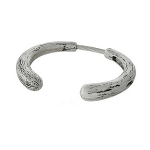Silver tone cuff bracelet with a bendable spring and brushed texture.