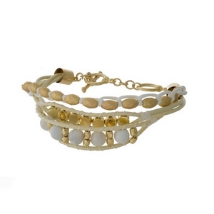Gold tone toggle bracelet with ivory leather cord and white beads.