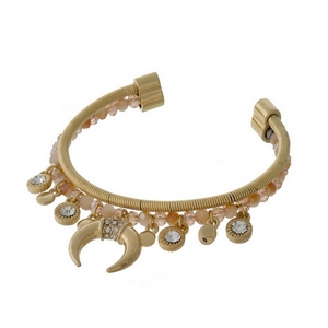 Gold tone and peach beaded cuff bracelet with a crescent charm and clear rhinestone accents.