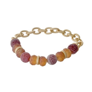 Matte gold tone stretch bracelet with carnelian natural stone beads and peach faceted beads.