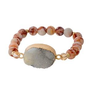 Peach beaded stretch bracelet with a white druzy stone focal.