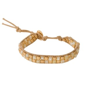 Two tone, beaded cord bracelet with a gold tone button closure.